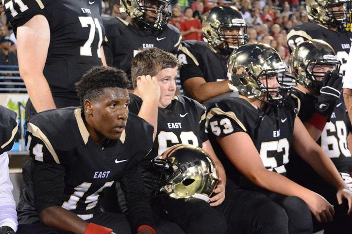 Football players brandish their brand new gold chrome helmets at the latest game in which they defeated Plano West 36-8.