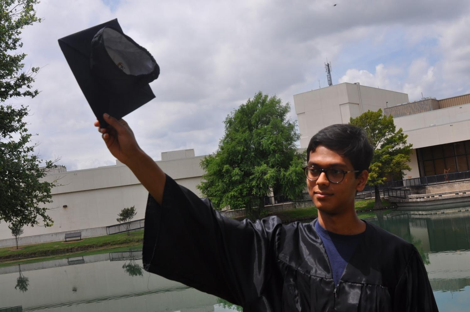 Senior Mohit Gupta celebrates his title of salutatorian by the school pond with a graduation cap and gown.