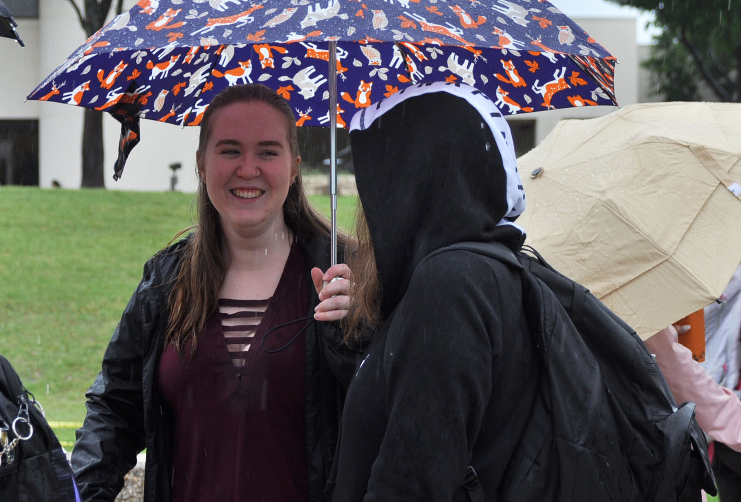 Junior+Samantha+Kling+laughs+in+the+rain+while+waiting+in+line+with+a+friend.