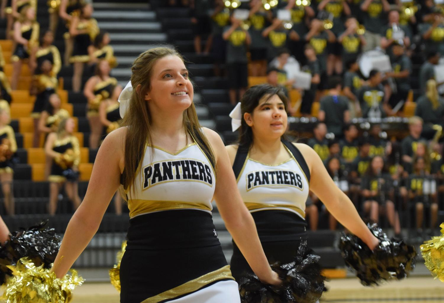 Senior Brooke Craghead and junior Vivian Easley cheer during the band performance at the Camp Panther pep rally on Aug. 3.