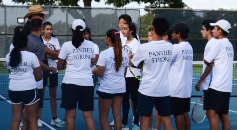 The JV tennis team holds a team meeting dring practice on Sept. 20.