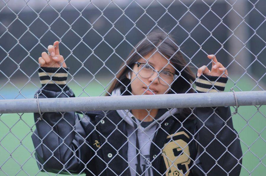 Senior Jennifer Chavira hides behind the fence leaving her eyes to tell the story.