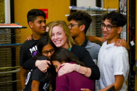 "Weide wraps students in a group hug after her surprise party. Senior IB HL art student Ismaeel Khan planned the event for Weide's last day during her fifth period class, bringing cake and pizza for everyone to enjoy. ""Ms. Weide has done so much for us,"" Khan said. ""This is the least we could do to repay her for all of her efforts."""