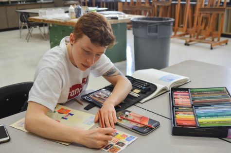 Junior Max Mosely works on an art project during B lunch Oct. 10. He recreated a photo of individually wrapped candies using Prismacolor colored pencils.