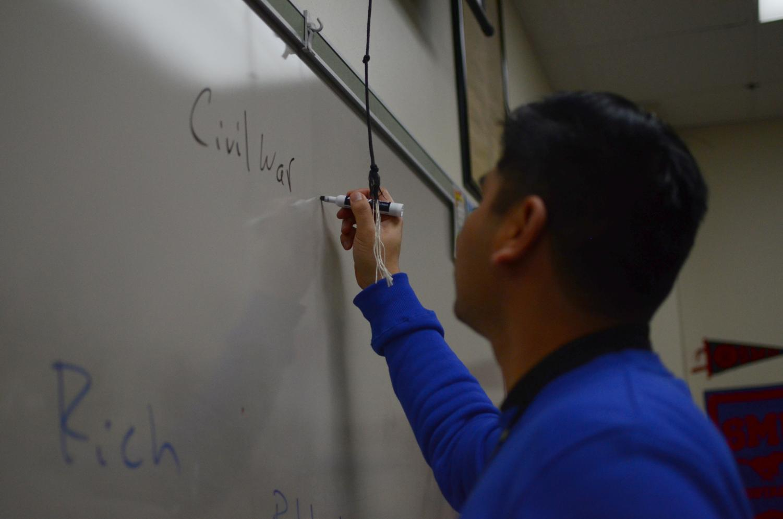 U.S. history teacher Dean Malabanan writes notes on the Civil War in class Dec. 13. Malabanan balances teaching with pursuing additional education.