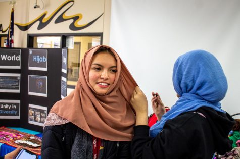"Freshman Mehreen Syed helps senior Lizzie Mortel tie a headscarf. Mortel wore the hijab along with her friends throughout the day. ""I thought that it was very eye-opening and involving,"" Mortel said. ""I felt like I was a part of a family."""