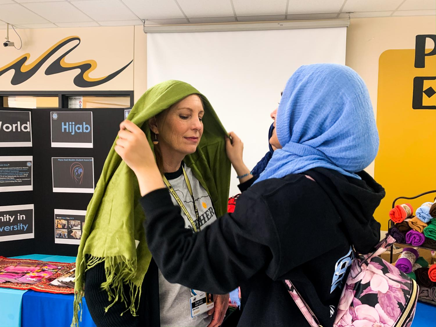Freshman+Mehreen+Syed+helps+assistant+special+education+teacher+Misti+Stolp+wear+a+headscarf.+Syed+was+one+of+many+students+volunteering+at+the+World+Hijab+Day+table.+%E2%80%9CThe+hijab+is+a+beautiful+symbol+of+freedom+and+diversity%2C%E2%80%9D+Syed+said.+%E2%80%9CWorld+Hijab+Day+celebrates+empowerment+and+unity%2C+and+as+a+high+school+Muslim+student%2C+I+loved+being+a+part+of+it.%E2%80%9D