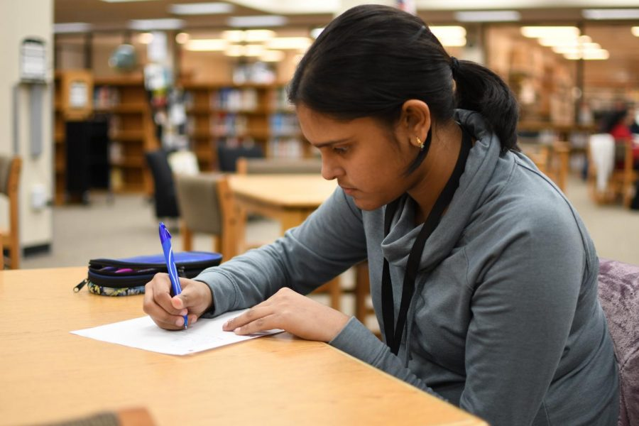 Freshman+Maryam+Ahmed+writes+a+poem+in+the+library+during+lunch+Nov.+14.